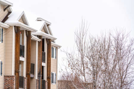 Snowy roof and small balconies viewed at the exterior of a residential building