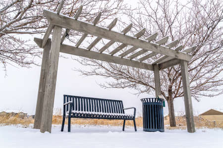 Winter landscape with outdoor bench and garbeage can under wooden pergola