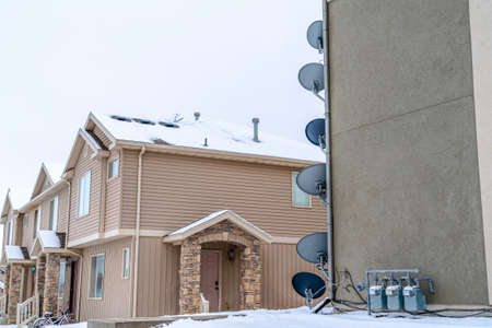 Satellite dishes antennas and electric meters on wall of residential building
