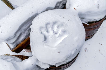 Handprint on thick layer of white snow on top of brown wooden barrel