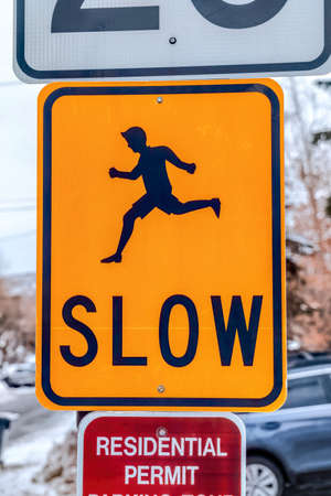 Close up of bright yellow Slow road sign with silhouetted image of running man Stockfoto