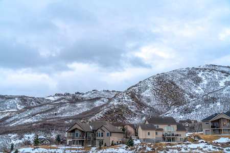 Homes nestled in the midst of snow dusted mountain slope viewed in winter Stock Photo