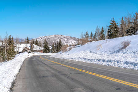 Park City landscape with paved mountain road on a scenic snowy scene in winter