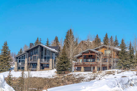 Facade of mountain homes in Park City Utah against blue sky on a winter setting