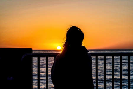 Woman with view of ocean and orange sun at sunset in San Diego California