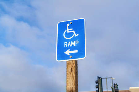Wheelchair Ramp with arrow sign against cloudy blue sky in San Diego California
