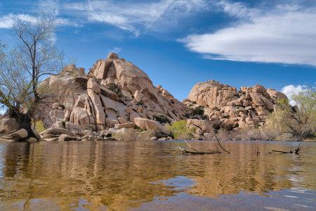 Big horn dam reservoir at Joshua Tree National Park against huge rocks and sky