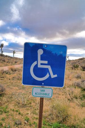 Handicapped parking sign against desert grassland at Joshua Tree National Park