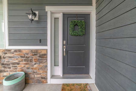 Entrance to a house with side light and gray front door decorated with wreath