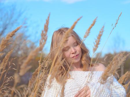 Beautiful pregnant woman in a white woolen sweater. Beautiful pregnant woman in high dry grass against the blue sky. Reklamní fotografie