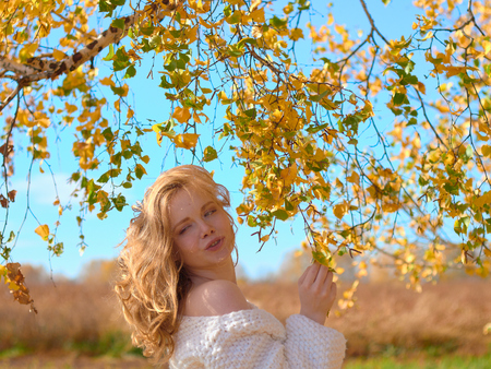Beautiful pregnant woman on nature under the birch leaves. Beautiful pregnant woman in a white woolen sweater. Stock fotó