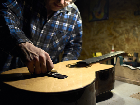 In the guitar workshop, Guitars Luthiers installs a saddle. Фото со стока