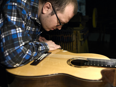 In the guitar workshop, Guitars Luthiers sets up a stand under the arm. Фото со стока