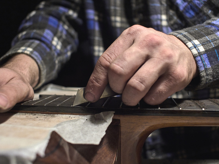 Installation frets on the neck of the guitar. The specialist cycles the fingerboard.