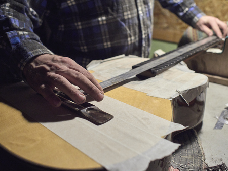 Installation frets on the neck of the guitar. The specialist checks the distance between the frets and the bridge.