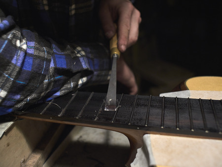 Installation frets on the neck of the guitar. The specialist removes excess glue from the fingerboard.
