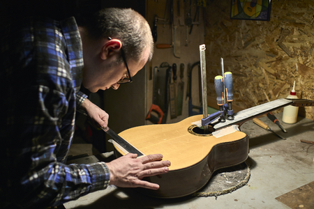 Fastening the neck to the Soundboard of the guitar.