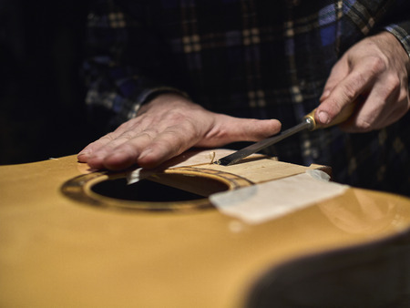 Fastening the neck to the Soundboard of the guitar. Removing the varnish from the Soundboard. Stock Photo