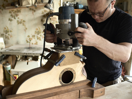 luthier carves a soundport in a guitar.