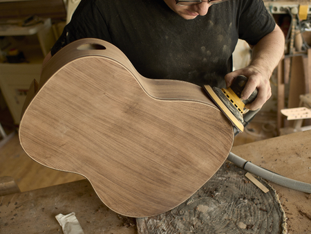 luthier polishes the body of a classical guitar. Reklamní fotografie