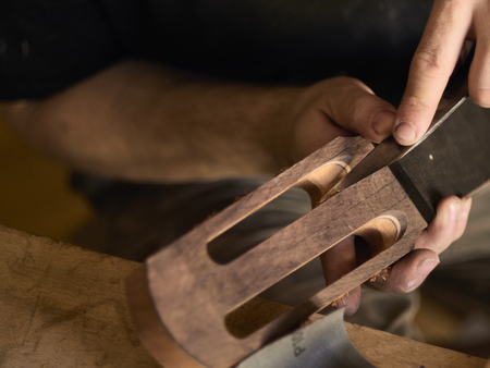 luthier makes head plate. Guitar master establishes an overlay on the head of the guitar.
