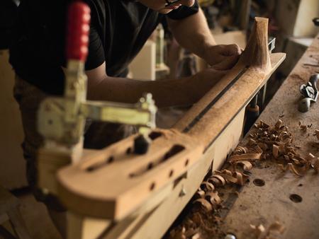 The guitar master makes a guitar neck. Imagens