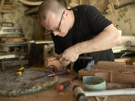 Luthier makes a neck block on a classical guitar.