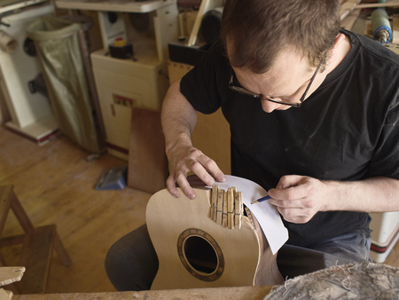 The process of making a cutaway on a classical guitar.
