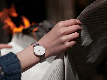Female hand with a clock on the background of burning fire. Stylish photograph of a watch with a white dial. Banco de Imagens - 121341784