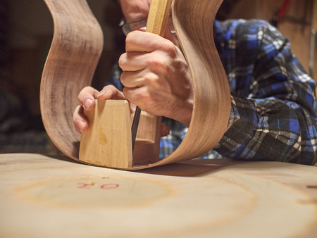 The process of making a classical guitar. Remove excess glue after gluing the tailblock.