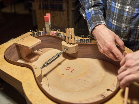 Glue lining to the side of the guitar. The process of making a classical guitar.