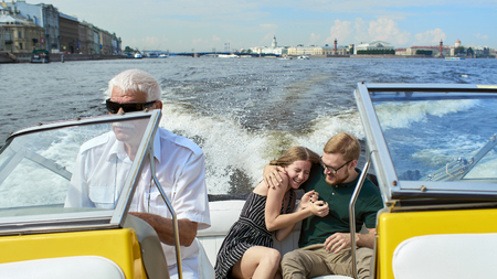 A young couple is traveling on a speedboat.