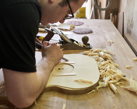 Marking and Pasting brace to the soundboard of a classical guitar. Production of classical guitar.