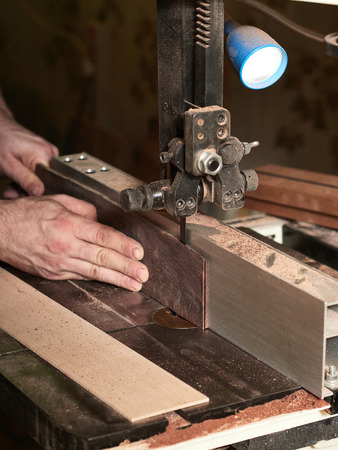 Production of classical guitar. Cutting off excess from the bar fretted with a band saw.