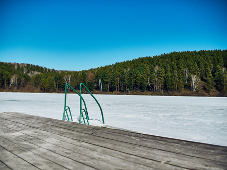 Cold Siberian landscape of a lake strained in the ice. frozen lake and ladder for diving into the water.