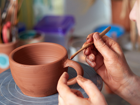 production process of pottery. The potter joins the cup and the handle from the cup.