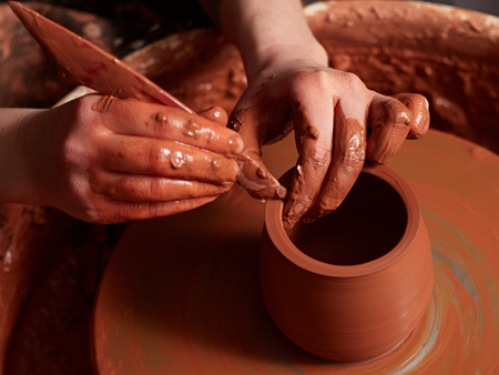 production process of pottery. Forming a clay teapot on a potter's wheel. Stock Photo