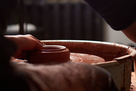 production process of pottery. Forming a clay teapot on a potters wheel.