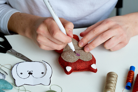 Step-by-step process of manual manufacturing baby crib mobile. Sketch the eye with a marker on the face.