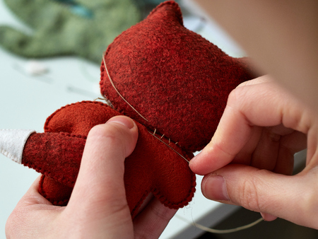 Step-by-step process of manual manufacturing baby crib mobile. Sewing a seam on a toy. 스톡 콘텐츠