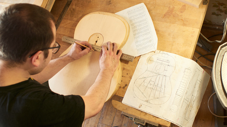 Marking and Pasting of footer and brace to the soundboard of a classical guitar. Production of classical guitar.