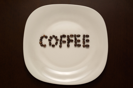 The inscription coffee is laid out on a plate of coffee beans.