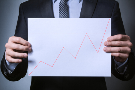 uptrend on the chart. a man in a business suit holding a sheet with the schedule of the uptrend. Stock Photo
