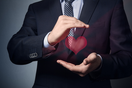 primo piano delle mani dell'uomo d'affari. un uomo in giacca e cravatta mostra un gesto premuroso. assicurazione sulla vita e sulla salute. Archivio Fotografico