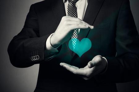 primo piano delle mani dell'uomo d'affari. un uomo in giacca e cravatta mostra un gesto premuroso. assicurazione sulla vita e sulla salute.