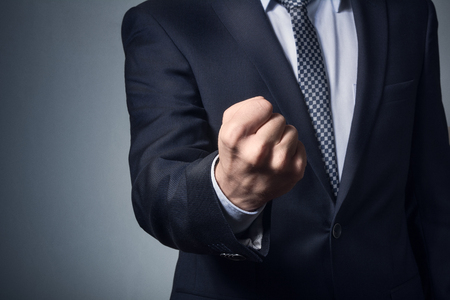 a man in a business suit. man business suit showing fist. Фото со стока