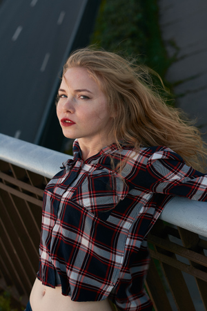 Blonde in a plaid shirt in windy weather on railway tracks. The blonde in a plaid shirt leaned on the railing.