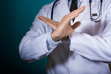 De dokter toont een gebaar met zijn armen gekruist over zijn borst. Een man in een doktersbadjas met een stethoscoop op een donkere turkooizen achtergrond, gebarend.