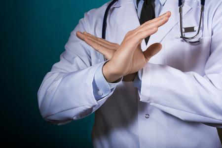 Lekarz pokazuje gest z rękami skrzyżowanymi na piersi. Mężczyzna w szlafroku lekarskim ze stetoskopem na ciemnym turkusowym tle gestykuluje.