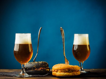 A traditional and black burger on a wooden table and with glasses full of foamy light beer. Stock fotó